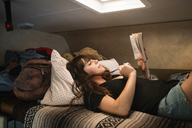 Woman reading book while relaxing on bed in camper van - CAVF23683