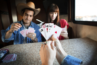 Close-up of woman holding cards while playing with friends in camper van - CAVF23686