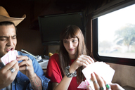 Couple playing cards while travelling in camper van - CAVF23689