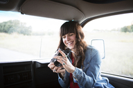 Cheerful woman using camera while travelling in camper van - CAVF23692