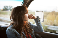 Thoughtful woman travelling in camper van looking out window - CAVF23695