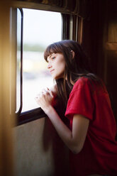 Thoughtful woman looking outside window while travelling in camper van - CAVF23707