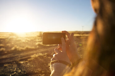 Woman photographing field with smart phone during sunset - CAVF23710