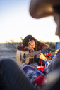 Woman leaning on guitar while sitting on field against sky - CAVF23758