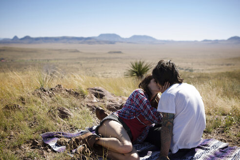 Couple kissing while sitting on field against clear sky - CAVF23779