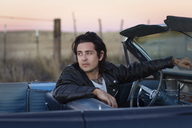 Young man looking away while sitting in convertible during sunset - CAVF23791