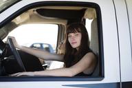 Portrait of woman looking through window while sitting in camper van - CAVF23815