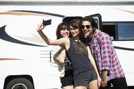 Friends taking selfie while standing by camper van - CAVF23818