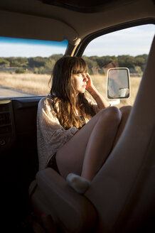 Thoughtful woman looking out of window while sitting in camper van - CAVF23824