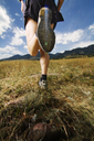 Low section of man running on grass field against sky - CAVF23884