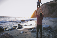 Rear view of playful father throwing son in air at beach - CAVF23887