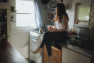 Thoughtful woman holding coffee cup while sitting on kitchen counter - CAVF23920