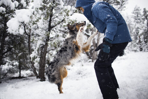 Side view of teenager playing with dog on snow covered field - CAVF23941