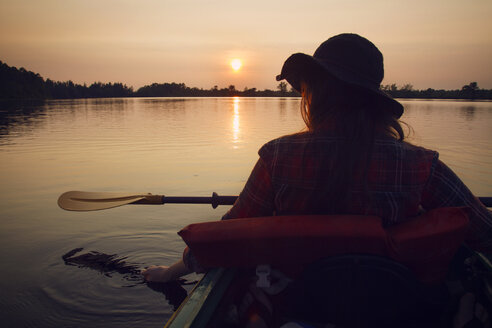 Rear view of woman kayaking in lake at forest during sunset - CAVF24067