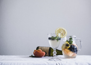 Cold drinks in glass and jug on table against white wall - CAVF24280