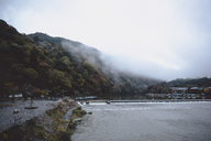 Scenic view of river by mountains during foggy weather - CAVF24289