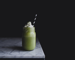 Close-up of matcha shake in bottle on marble counter against black background - CAVF24349