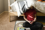 Boy sitting against bunkbed with blanket on head - CAVF24433