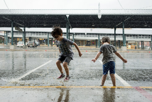 Happy brothers playing in parking lot during monsoon - CAVF24445