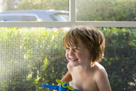 Cheerful boy looking away while playing with toy at home - CAVF24561