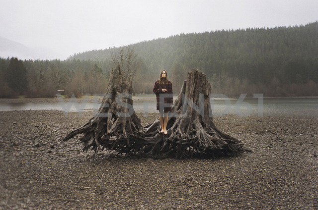 Woman standing on driftwood shore by Rattlesnake Lake - CAVF24585