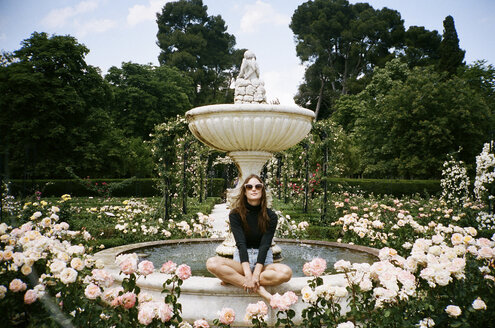 Portrait of woman sitting on fountain surrounded by roses in park - CAVF24594