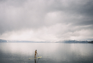 Woman paddleboarding on lake against cloudy sky - CAVF24600