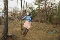 Playful girl in rabbit mask swinging in backyard - CAVF24633