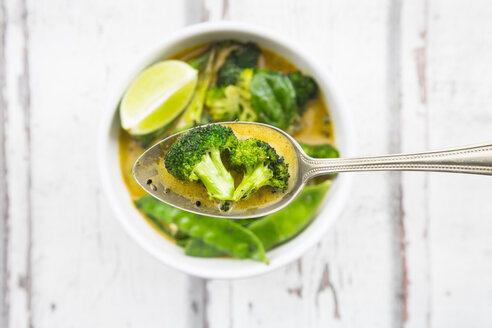 Green thai curry with broccoli, pak choi, snow peas, baby spinach, lime, broccoli and sauce on spoon - LVF06817