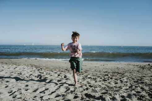 Carefree boy running at beach against clear sky during sunny day - CAVF24716