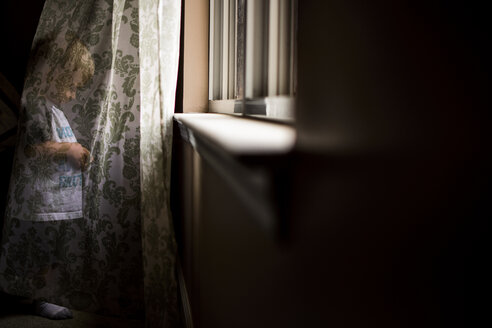 Playful boy hiding behind curtain at home - CAVF24725