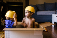 Playful brothers with bowls on head sitting in cardboard box at home - CAVF24740