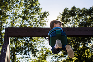 Low angle view of boy swinging against sky in playground - CAVF24761
