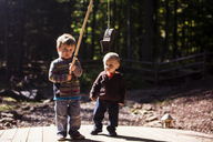 Boy looking at brother holding artificial fish in playground - CAVF24770