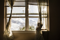 Boy playing with curtain by window at home - CAVF24791