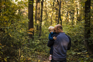 Father carrying son while standing in forest - CAVF24800