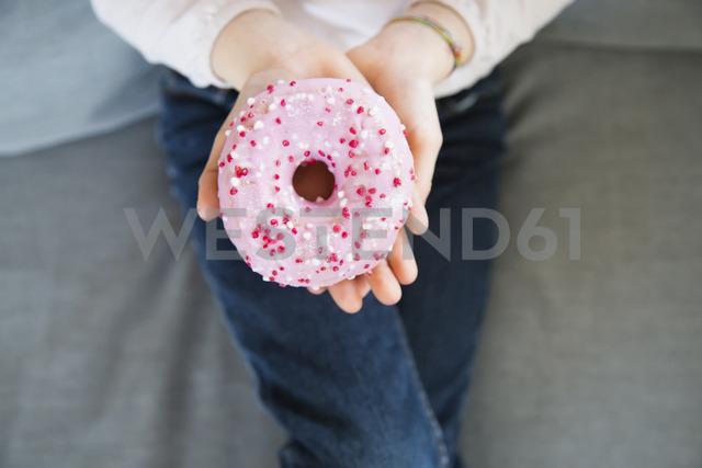 Girl's hand holding pink doughnut, close-up - LVF06819