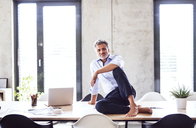Portrait of smiling mature businessman sitting barefoot on desk in office - HAPF02651