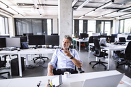 Mature businessman sitting at desk in office using smartphone - HAPF02675