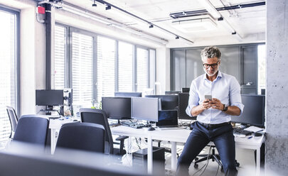 Smiling mature businessman sitting on desk in office using smartphone - HAPF02690