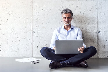 Portrait of confident mature businessman sitting on the floor using laptop - HAPF02696