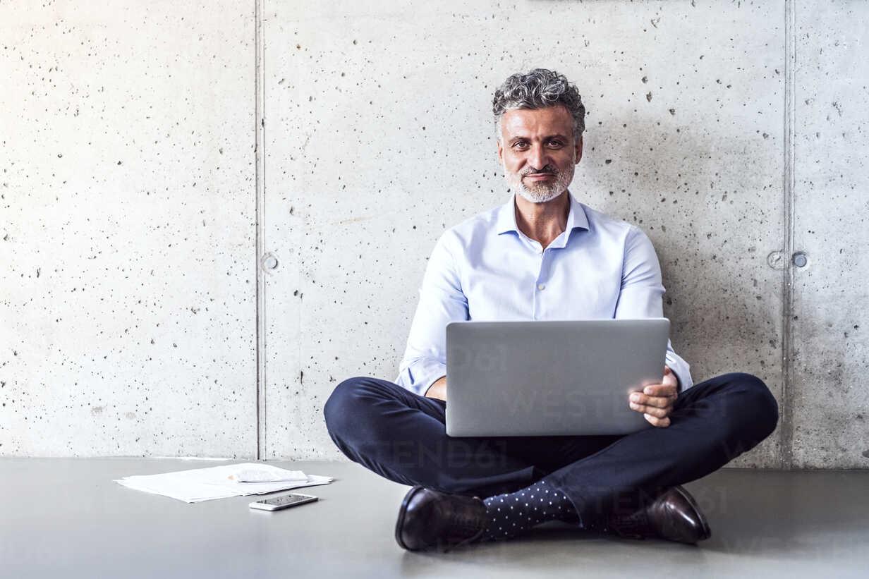 Portrait of confident mature businessman sitting on the floor using laptop - HAPF02696 - HalfPoint/Westend61