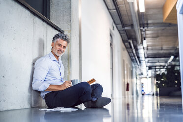 Portrait of smiling mature businessman sitting on the floor - HAPF02699