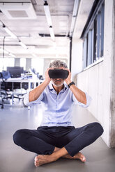 Barefoot mature businessman sitting on floor in office wearing VR glasses - HAPF02714