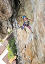 Thailand, Krabi, Tonsai beach, woman climbing in rock wall - ALRF01031