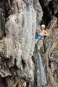 Thailand, Krabi, Lao Liang, barechested climber in rock wall - ALRF01037