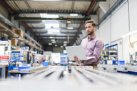 Young businessman using laptop in production hall - DIGF03492