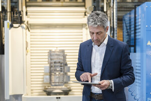 Businessman using tablet in production hall - DIGF03525