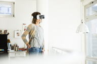 Woman wearing VR glasses at home - MOEF00925