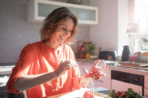 Smiling woman making strawberry jam in kitchen at home - MOEF00934